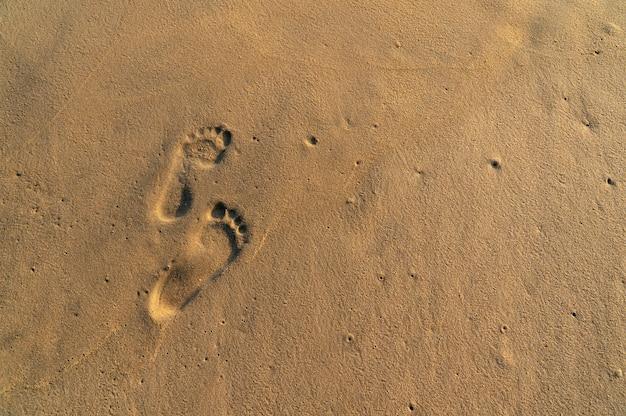 Des pas sur la plage de sable jaune.