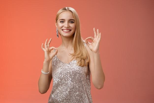 Pas de problème ami. charmante femme européenne blonde tendre et insouciante en robe argentée montrer ok geste ok souriant heureux recommander une fête géniale assurer de s'amuser, sentir un excellent fond rouge.