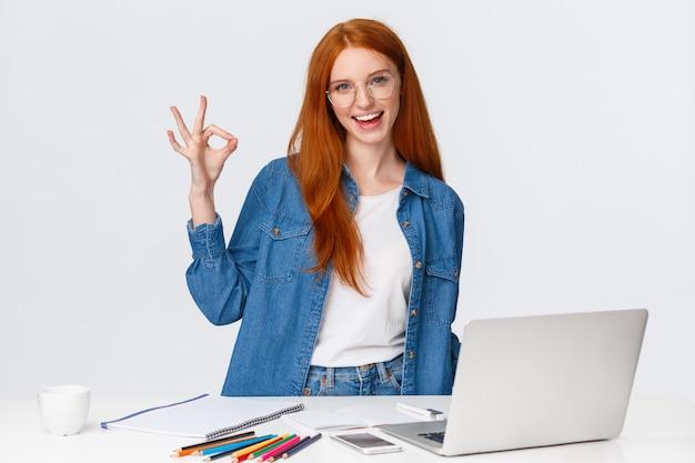 Pas de problème, tout est excellent. femme rousse créative confiante avoir un plan, préparer un projet de conception, travailler avec l'équipe sur le dessin, debout près de la table avec un ordinateur portable, des crayons de couleur, montrer ok
