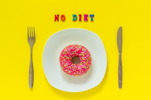 Pas de régime et beignet rose sur une assiette blanche et une fourchette à couteau sur fond jaune.