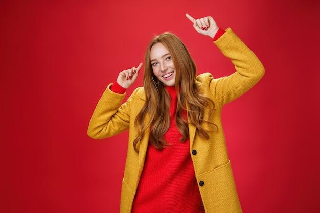 Pas le temps de danser le chagrin et de se sentir heureux, l'automne est venu. portrait d'une femme rousse charmante, lumineuse et joyeuse, levant les mains au rythme de la musique ravie de poser en manteau jaune sur un mur rouge.