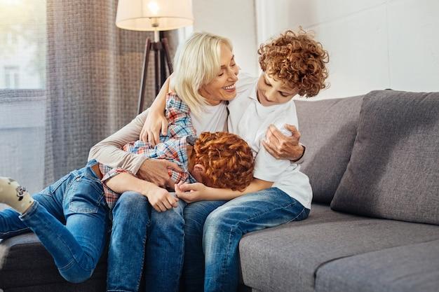 Pas le temps de s'inquiéter. garçons aux cheveux bouclés plaisantant et s'amusant assis sur un canapé et passant le week-end dans une maison de grand-mère.