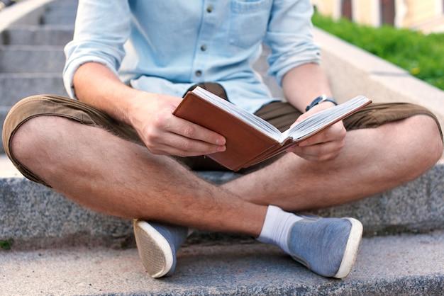 Pas de visage. étudiant avec livre assis sur les escaliers du campus
