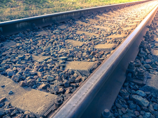 Passage à niveau, voie ferrée. des rails partent au loin au coucher du soleil.