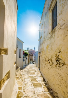 Passage pavé étroit typiquement rustique entre d'anciens murs de pierre à midi à lefkes, grèce