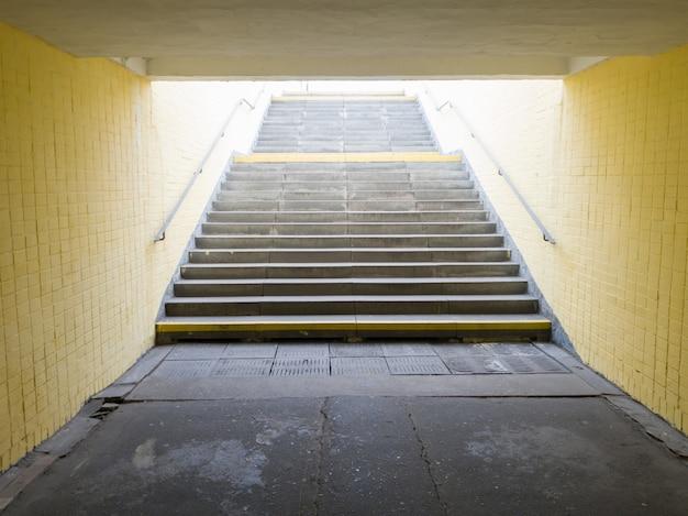 Passage pour piétons souterrain jaune vide. tunnel et lumière du jour au bout. marches vers le haut au passage pour piétons. un long tunnel en béton avec des lanternes dans le sous-sol de la ville.