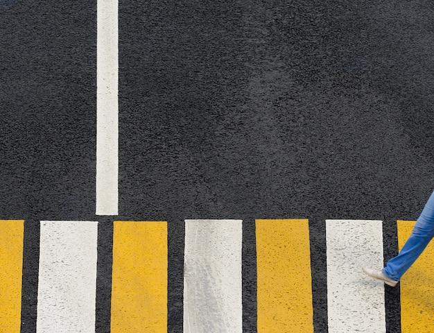 Passage pour piétons zébré sur une route goudronnée avec piéton