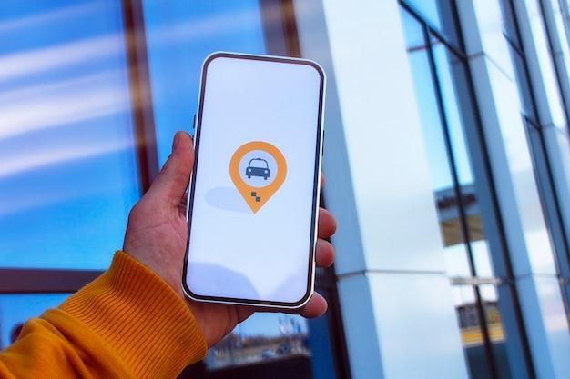 Un passager dans le parking tient un smartphone avec une application mobile et appelle un taxi en ligne.