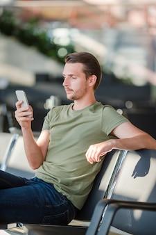Passager dans un salon d'aéroport en attente d'un avion, jeune homme avec téléphone portable à l'aéroport en attente d'atterrissage