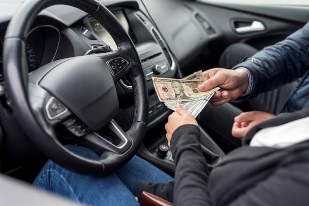 Passager donnant des billets en dollars à un conducteur
