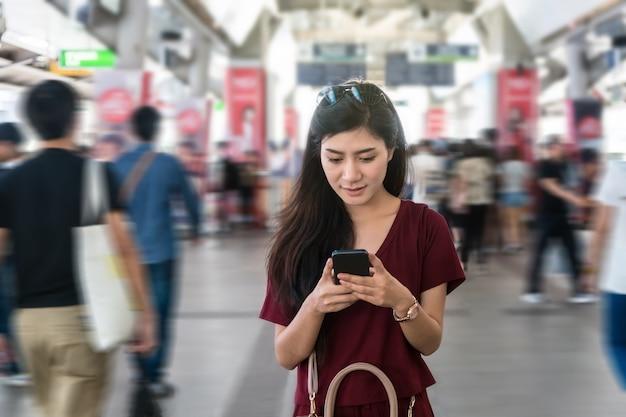 Passager de femme asiatique avec un costume décontracté en utilisant le téléphone mobile intelligent