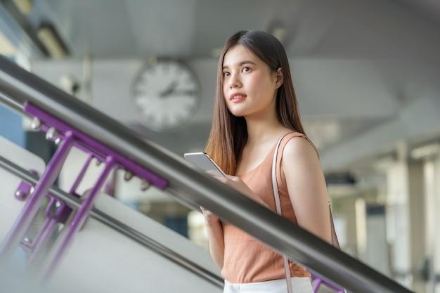 Passager d'une jeune femme asiatique portant un casque et utilisant un téléphone mobile intelligent