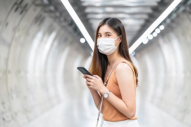 Passager d'une jeune femme asiatique portant un masque chirurgical et regardant la caméra dans le métro