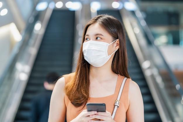Passager d'une jeune femme asiatique portant un masque chirurgical et utilisant un téléphone portable intelligent