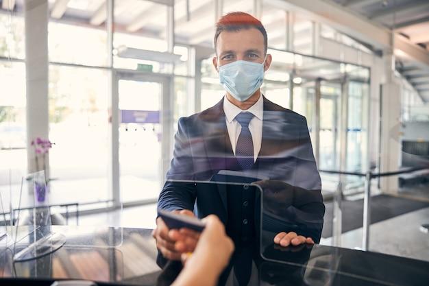 Passager responsable portant un masque de protection faisant vérifier ses documents à l'aéroport