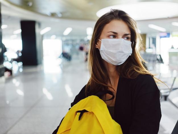 Un passager avec un sac à dos jaune portant un masque médical est assis à l'aéroport
