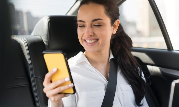 Passagère utilisant son téléphone portable dans la voiture