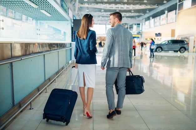 Passagers en classe affaires avec bagages à l'aéroport, vue arrière.