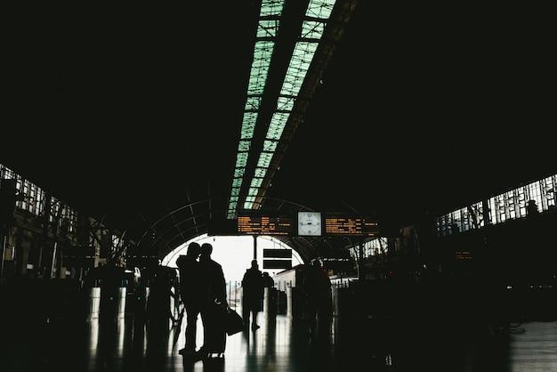 Les passagers à la gare attendent avec leurs bagages pendant les vacances.