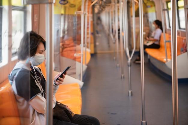 Passagers regardant les téléphones portables dans le train électrique bts à bangkok en thaïlande