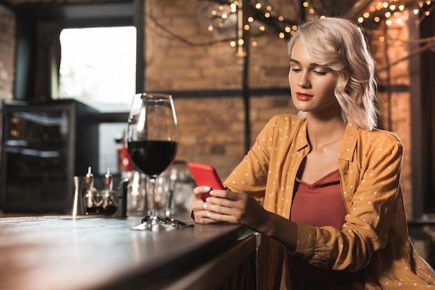 Passe-temps agréable. charmante jeune femme assise au comptoir du bar et surfer sur internet tout en buvant un verre de vin rouge