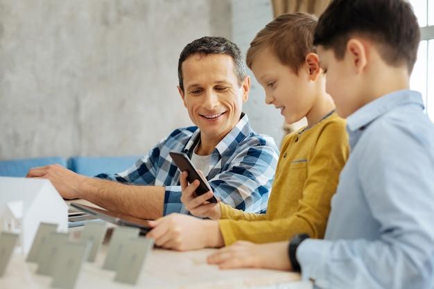 Passe-temps agréable ensemble. garçons pré-adolescents optimistes montrant à leur père une vidéo au téléphone et la regardant avec lui pendant que l'homme travaille dans son bureau