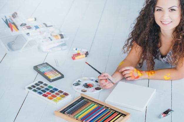 Passe-temps artistique et loisirs. peinture de femme. crayons de couleur, palette aquarelle et toile au sol.