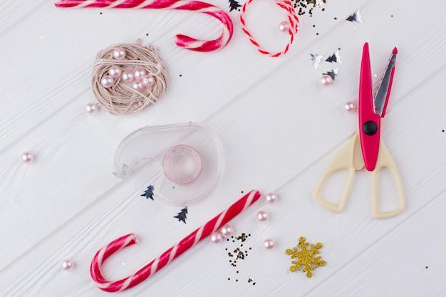 Passe-temps créatif de bricolage. espace de travail de vacances de noël avec des ciseaux, des cannes de bonbon, de la ficelle et des décorations scintillantes. préparation de noël et nouvel an.