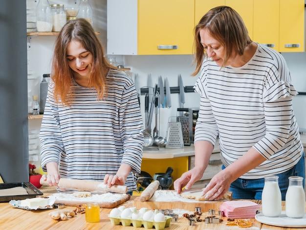 Passe-temps de cuisine familiale. mère et fille cuisiner ensemble, rouler la pâte pour faire des biscuits en pain d'épice.