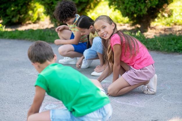 Passe-temps, été. fille heureuse aux longs cheveux blonds avec des amis dans des vêtements décontractés confortables, dessin avec des crayons dans le parc par une journée ensoleillée