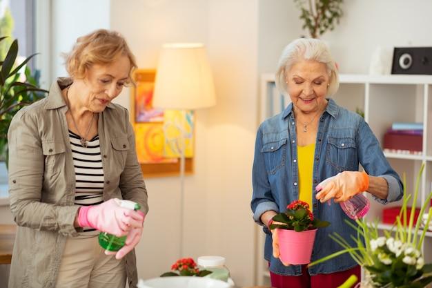 Passe-temps favori. belles femmes positives souriantes tout en appréciant le jardinage