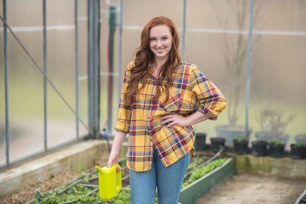Passe-temps favori. heureuse jeune femme adulte avec de longs cheveux roux avec un arrosoir vert clair debout dans une serre d'humeur optimiste