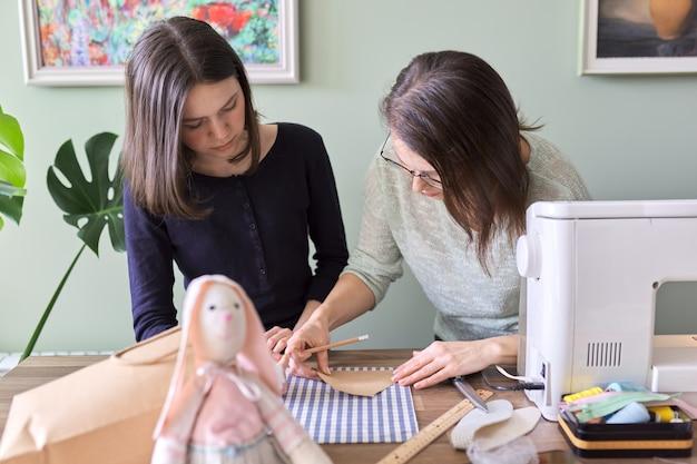 Passe-temps et loisirs créatifs en famille, mère et fille adolescente cousent ensemble une poupée de lapin. la femme enseigne des techniques de couture de fille, parlant