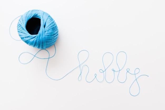 Passe-temps de mot fait de fil bleu, de perles et de crochets sur une surface blanche,
