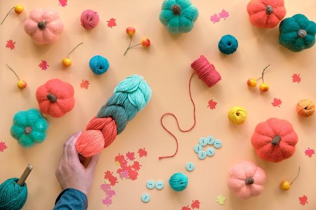 Passe-temps à plat. fond saisonnier d'automne avec des citrouilles en laine feutrée bricolage, un paquet de laine, des boutons et des baies.