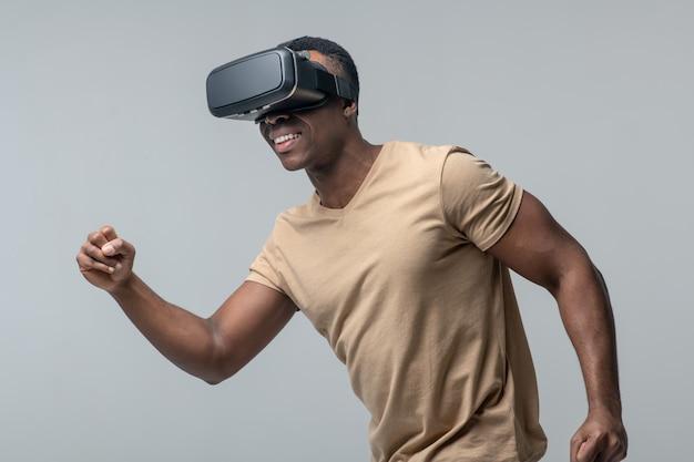 Passe-temps, stimulation 3d. jeune adulte afro-américain actif dans des verres virtuels intéressés se déplaçant en studio sur fond clair