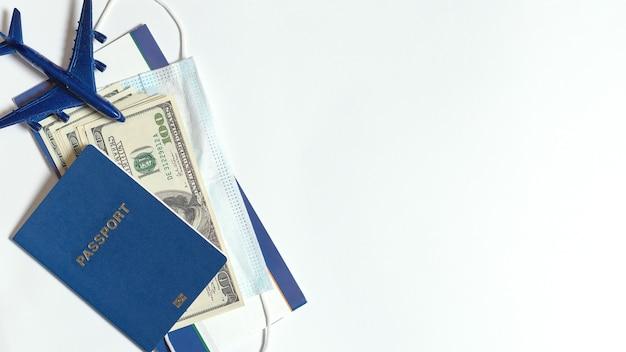 Passeport et argent en dollars masque et figurine d'avion sur fond blanc
