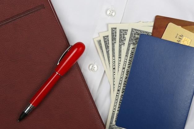 Passeport, argent, stylo, cahier et cartes bancaires sont sur une chemise blanche à manches