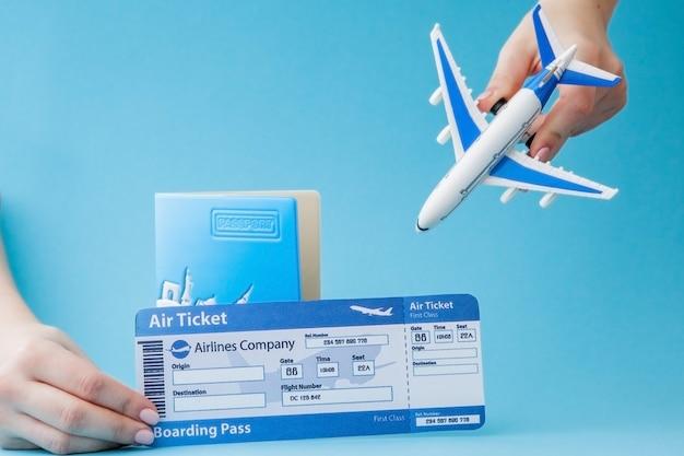 Passeport, avion et billet d'avion en main de femme sur bleu