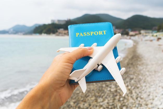 Passeport et avion jouet en main sur le fond de la mer, concept de voyage