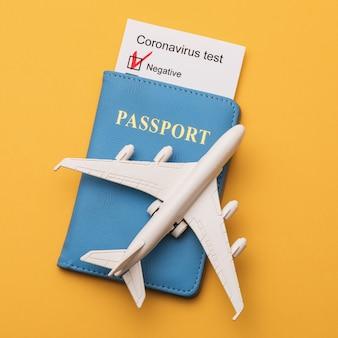 Passeport d'avion jouet et résultats des tests de coronavirus sur une surface jaune