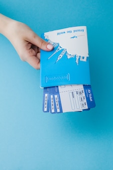 Passeport et billet d'avion en main de femme sur fond bleu. concept de voyage, espace copie