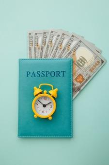 Passeport avec billets en argent et réveil sur bleu.
