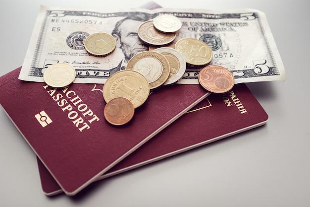 Passeport avec des billets et des pièces sur un fond uni.