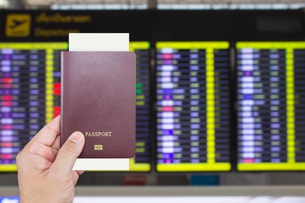 Passeport avec carte d'embarquement en main masculine avec écran d'affichage des informations de départ de vol flou