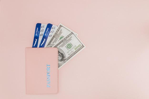 Passeport, dollars et billet d'avion sur fond rose. concept de voyage, espace copie