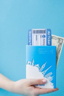 Passeport, dollars et billet d'avion en main de femme sur bleu