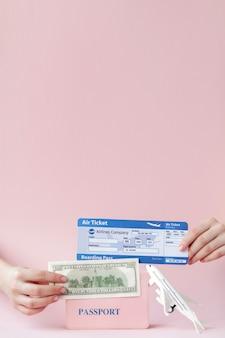 Passeport, dollars et billet d'avion en main de femme sur fond rose. concept de voyage, espace copie