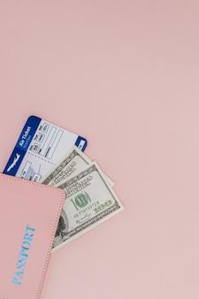 Passeport, dollars et billet d'avion sur une surface rose. concept de voyage, espace de copie.