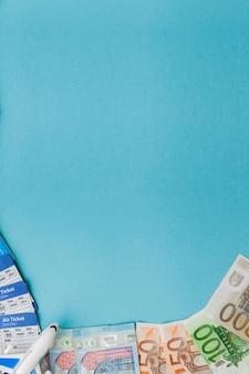 Passeport, dollars et euros, billet d'avion et d'avion sur fond bleu. concept de voyage, espace de copie